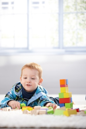 Ginger-haired toddler playing with building cubes, laying on floor at home. photo