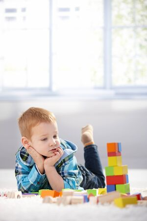 Adorable gingerish little boy laying on floor, playing with building cubes. photo