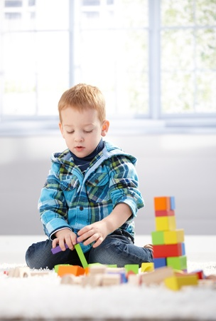 babies playing: Ginger-haired toddler playing on floor with building cubes. Stock Photo