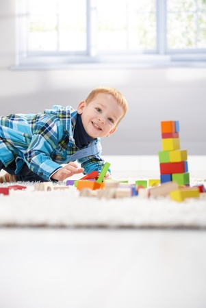 Happy little boy playing with building cubes at home on floor. Stock Photo