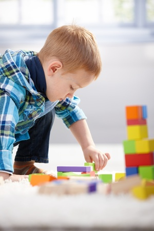 3 year old: Lovely 3 year old boy lost in playing with building cubes at home on floor.