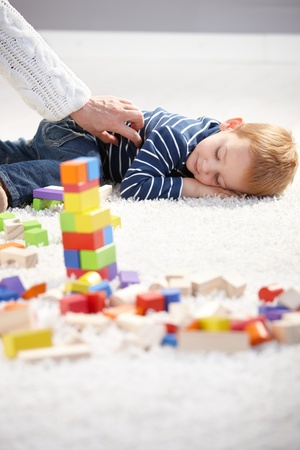 Sweet little boy getting tired in playing, laying on floor, among cubes. photo