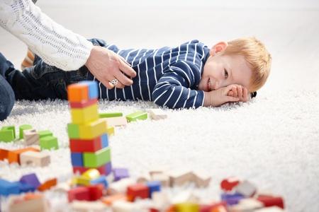 gingerish: Dulce ni�o chico puesta en piso, sonriendo como madre le cosquillas.