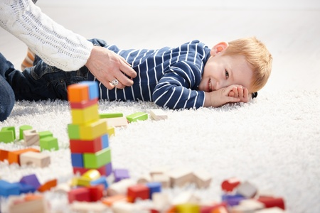 Sweet toddler boy laying on floor, smiling as mother tickling him. photo