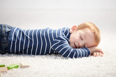blue carpet: Cute 3 year old boy falling asleep on floor at home.
