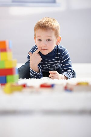 Sweet little boy laying on floor, playing with building cubes, thinking. photo