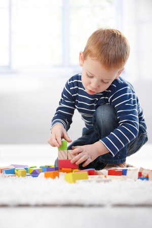 3 year old boy: Ginger-haired little boy playing at home with building cubes, concentrating.
