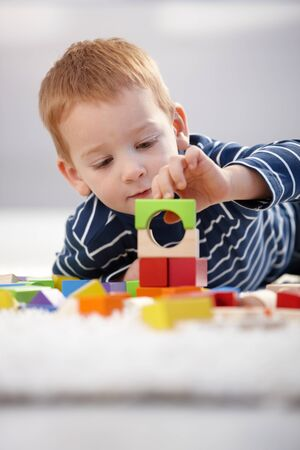 Sweet gingerish little boy building tower from cubes at home, laying on floor. photo