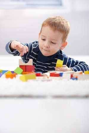 prone: Cute little kid playing on floor with building cubes at home. Stock Photo