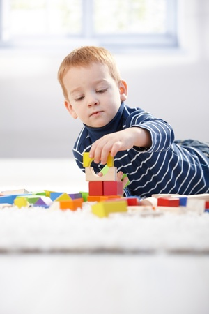 3 persons only: Lovely 3 year old playing with building cubes at home, laying on floor. Stock Photo