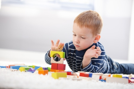 Sweet little boy laying on floor, playing with building cubes.