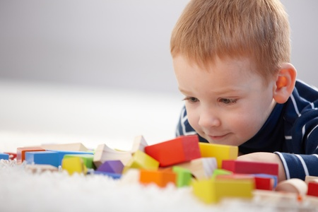 three persons only: Adorable ginger-haired little boy playing with cubes, smiling. Stock Photo