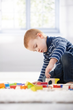 3 year old boy: Gingerish little boy playing with building cubes at home on floor.