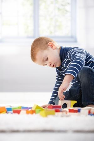 gingerish: Gingerish ni�o jugando con cubos en casa en piso de edificio.
