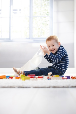 Happy little boy playing on floor, having cubes and plastic bag.