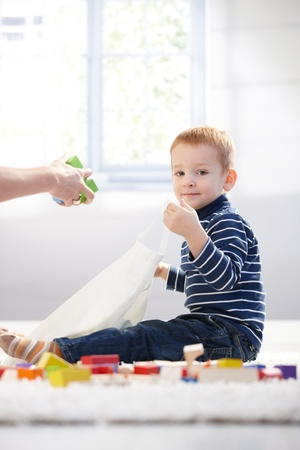 Cute kid packing toys to plastic bag, playing at home on floor. photo