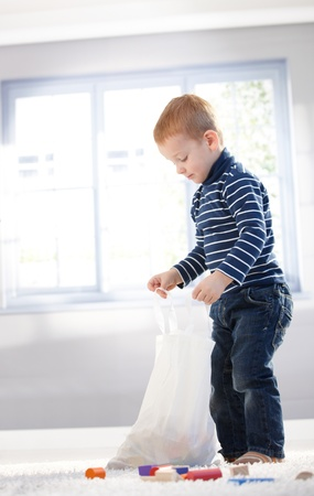 plastic toys: Cute little boy playing, unpacking bag with toys at home.