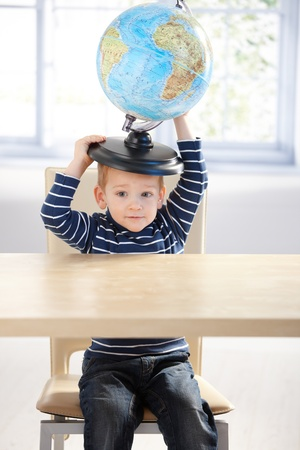Cute little boy sitting at desk, holding globe on head, having fun. photo