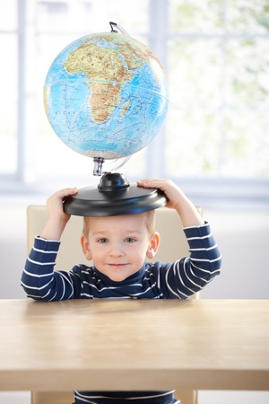 3 year old boy: Adorable 3 year old boy having fun with globe, sitting at desk, smiling.