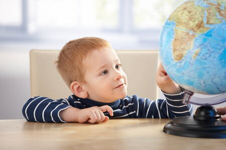 Sweet little scholar studying globe, sitting at desk. photo