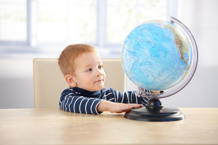 Sweet ginger-haired little boy studying globe, sitting at desk. photo