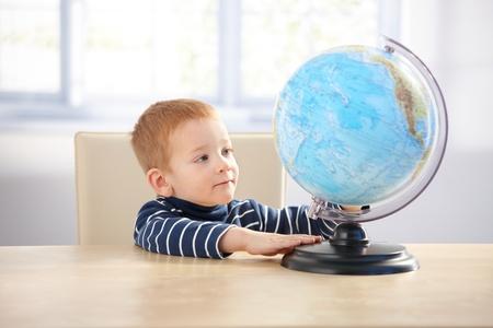 Sweet ginger-haired little boy studying globe, sitting at desk. photo