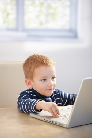 Sweet gingerish kid playing video game on laptop at home, smiling. photo