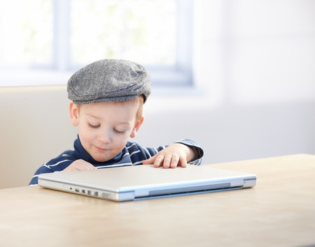 Sweet little kid sitting at table, wearing cap, playing with laptop. photo