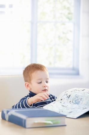 gingerish: Gingerish kid estudiando cyclopaedia en casa, sentado a la mesa.