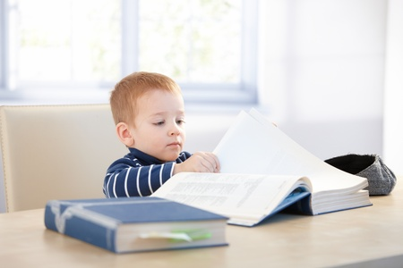 Little kid playing schoolboy, sitting at table, looking at encyclopedia. photo