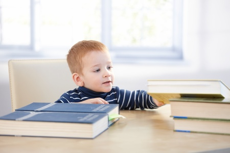 Lovely toddler acting like schoolboy, having books. photo