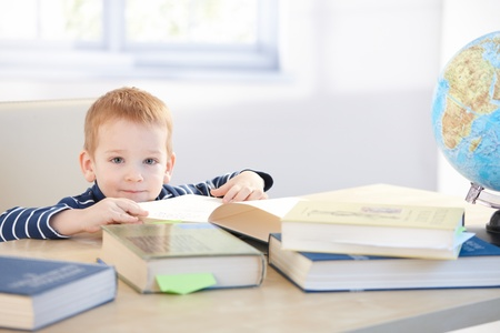 Little child prodigy learning at home, sitting at table, smiling. photo