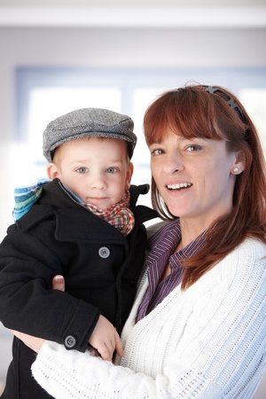 Mother holding son in arms, smiling happily. photo