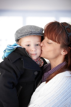 be kissed: Mother holding cute toddler in arms, kissing.