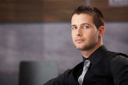 Young handsome businessman sitting in modern office. photo