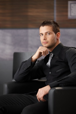 Handsome businessman waiting in office lobby, sitting in armchair. photo