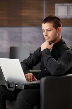 young unshaven: Young businessman working on laptop, sitting in armchair in office lobby.
