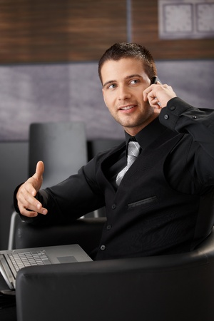 Goodlooking young businessman chatting on phone, sitting in meeting room. photo