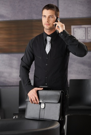 Handsome businessman standing in office lobby, talking on mobile phone. photo