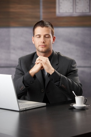 resting: Businessman meditating at desk in office.