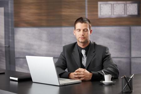 man meditating: Top manager meditating in elegant office, sitting at desk.