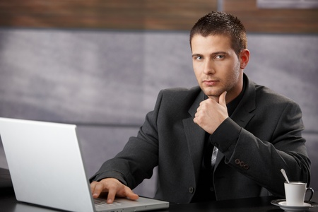 Goodlooking manager sitting at desk, using laptop in elegant office. photo