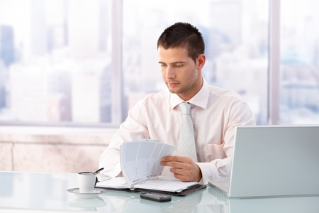 Young handsome businessman looking at organizer in bright office. photo