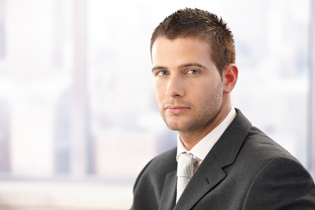 severity: Portrait of young businessman in bright office.