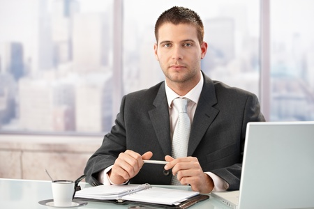 Elegant businessman sitting at desk in bright office. photo