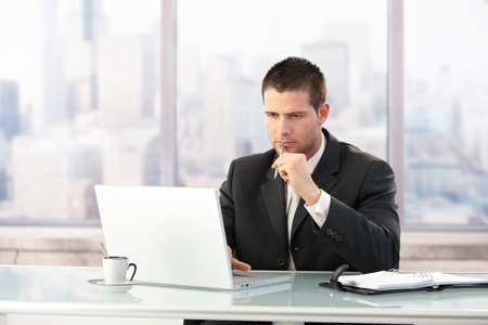 Young manager sitting at desk in bright office, working on laptop.