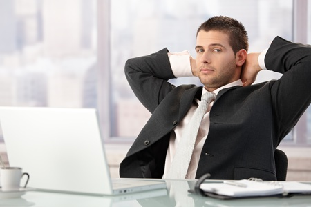 Young businessman relaxing in office, sitting at desk. photo