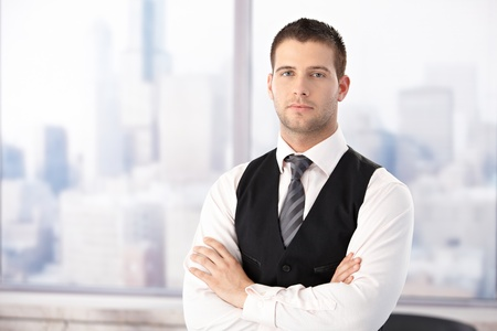 stubbly: Portrait of young handsome businessman in bright office, standing arms crossed.