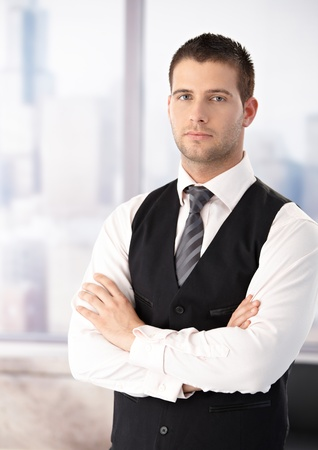 offish: Portrait of young businessman standing arms crossed, wearing waistcoat.