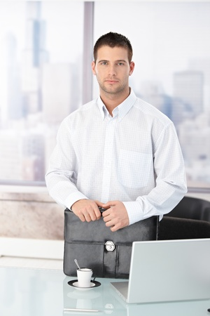 Casual office worker standing in bright office, having briefcase. photo